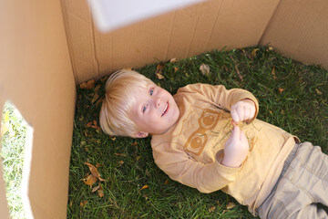 Boy lying down in a cardboard house in backyard