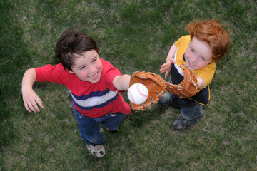 Two boys with baseball gloves playing a catch