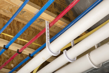 Blue and red cables and white pipes on ceiling