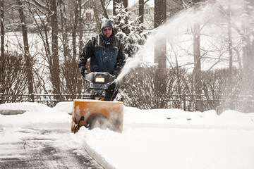 Man using snowblower in cold winter