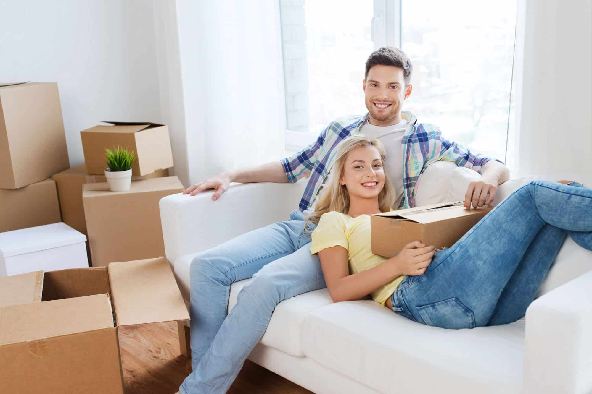 A couple sitting on the couch while unpacking
