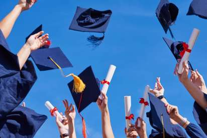 Graduates tossing up hats over blue sky