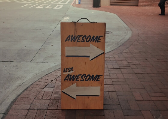 Wooden street signboard with right arrow awesome and left arrow less awesome