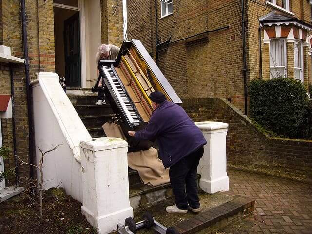 Piano movers carry piano downstairs.
