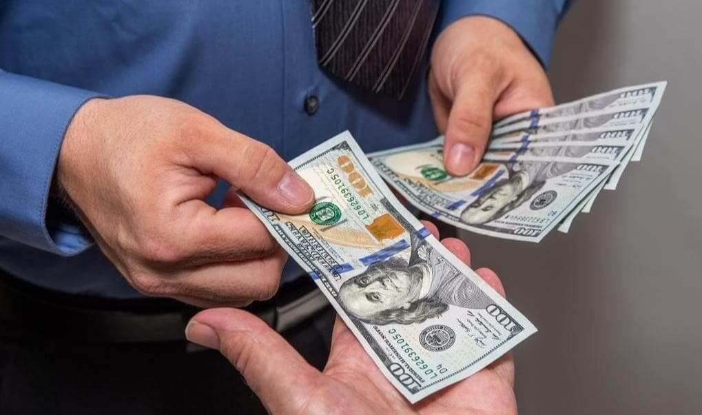 handing a $100 bill to a vendor