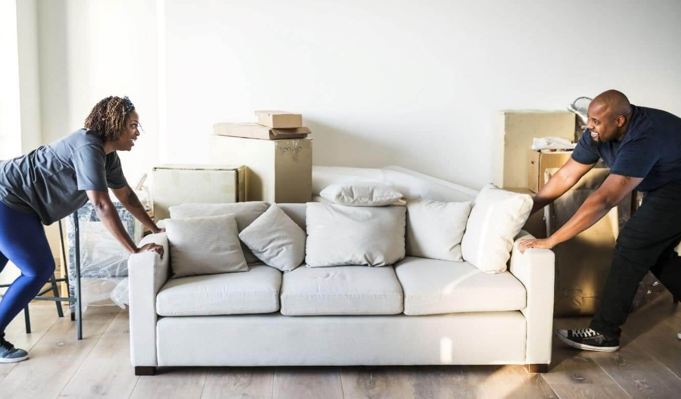 Couple moving white couch in apartment