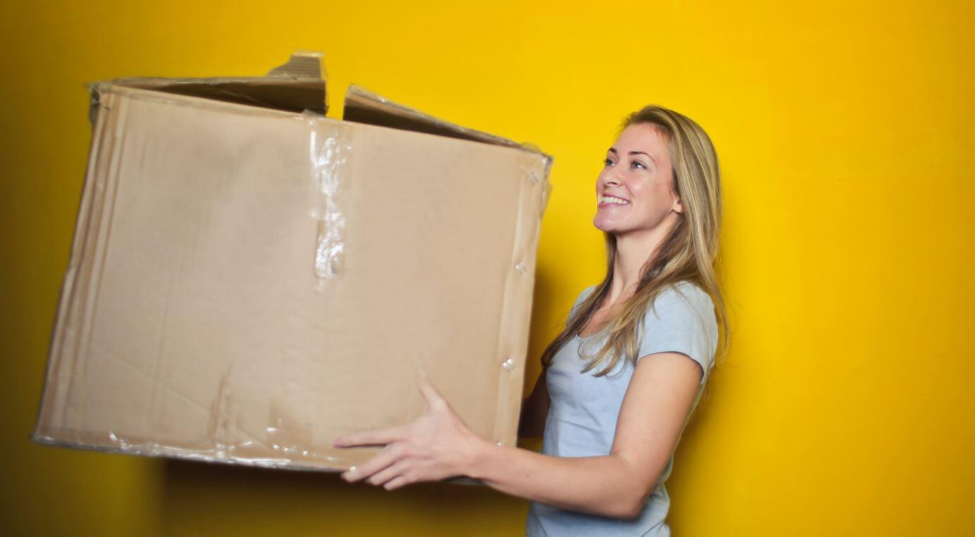 Blonde lady carries a moving cardboard box
