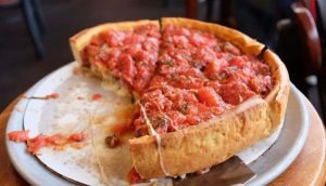 Pizzeria Uno and Due deep dish pie with a spatula
