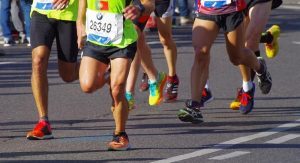 runners with numbers and shoes on road