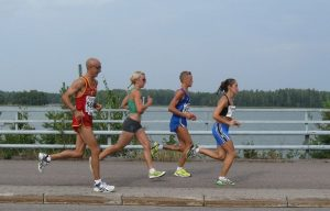 four people running in marathon along a lake